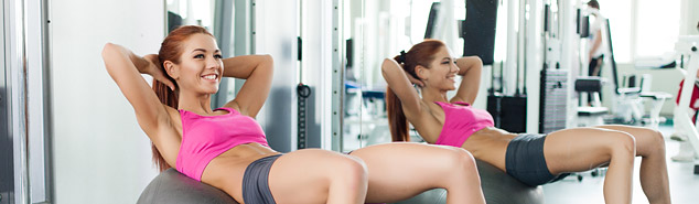 woman working out in gym in front of glassless mirror